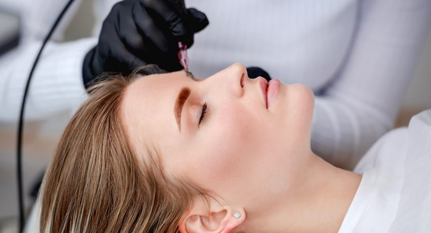 Face of girl in profile during microblading permanent makeup process. Hands of tattoo master holding professional ink machine with medicine needle